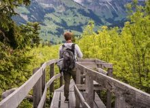 boy with backpack on walking with green views