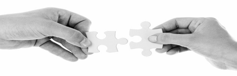 2 hands holding pieces of jigsaw puzzle