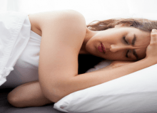 woman lay in bed with headache on white bedding