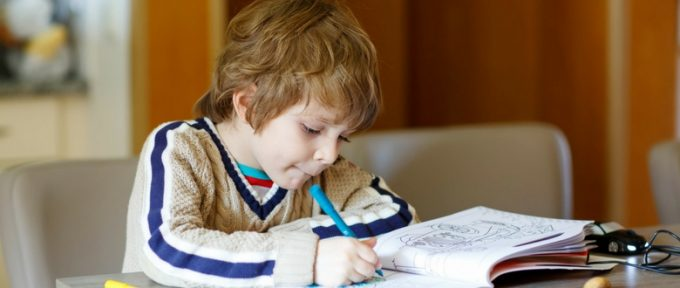 young boy colouring in colouring book