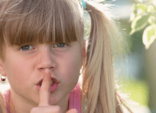 little girl with finger on her lips in quiet environment