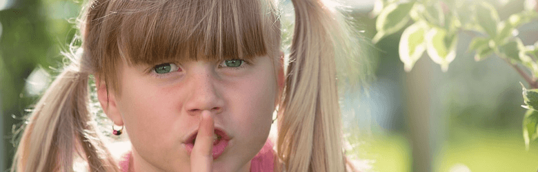 little girl with blonde hair and finger on her lips