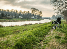 abandoned wheelchair on the field by the river