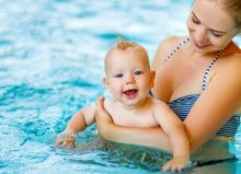 baby swimming in pool with their parent