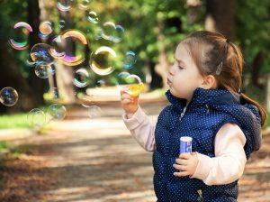 little girl blowing bubbles