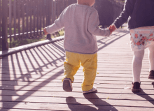 two children walking across a bridge